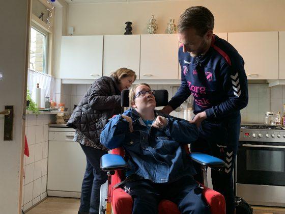 Willem Janssen van FC Utrecht verrast mantelzorger An Doornkamp in Driebergen en helpt dochter Debbie in haar jas om samen boodschappen te doen in het kader van Mantelzorgcampagne Zorg van de Zaak en FC Utrecht